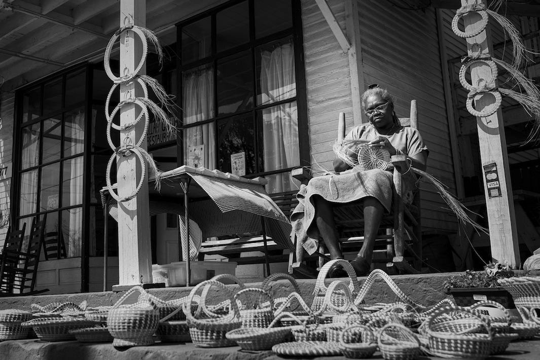 Jery Bennet Taylor sews sweetgrass baskets on the porch at Gullah Grub Restaurant. Photo courtesy Pete Marovich
