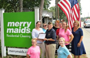 Chuck Luray of American Legion Post #9 presents a certificate of recognition to Merry Maids of Beaufort for proudly flying the U.S. Flag outside of their business.